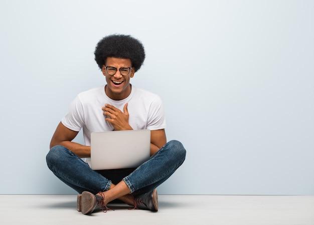 Junger schwarzer mann, der auf dem boden mit einem laptop lacht und spaß hat sitzt