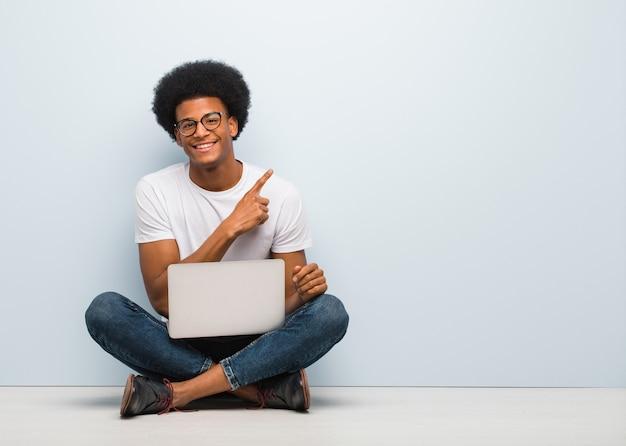Junger schwarzer mann, der auf dem boden mit einem laptop lächelt und auf die seite zeigt sitzt