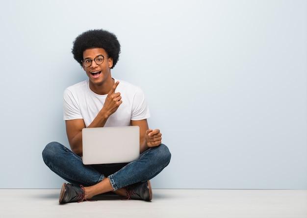 Junger schwarzer mann, der auf dem boden mit einem laptop sitzt, der mit finger zur seite zeigt
