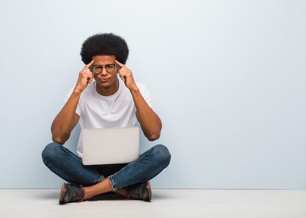 Junger schwarzer mann, der auf dem boden mit einem laptop tut eine konzentrationsgeste sitzt