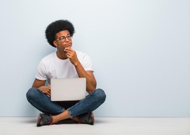 Junger schwarzer mann, der auf dem boden mit einem laptop zweifelt und verwirrt sitzt