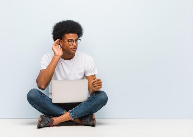 Junger schwarzer mann, der auf dem boden mit einem laptopversuch zum hören eines klatsches sitzt