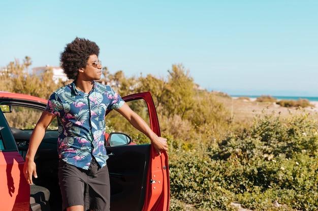 Junger schwarzer mann, der aus auto auf natur herauskommt