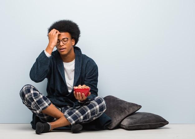Junger schwarzer mann, der besorgt und überwältigt sitzt und frühstückt