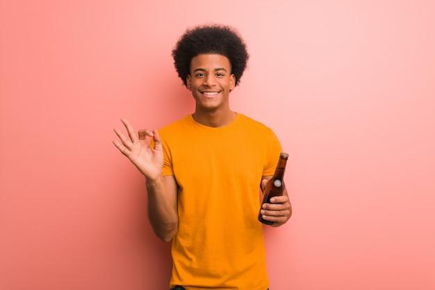 Junger schwarzer mann, der ein bier nett und überzeugt hält, okaygeste tuend