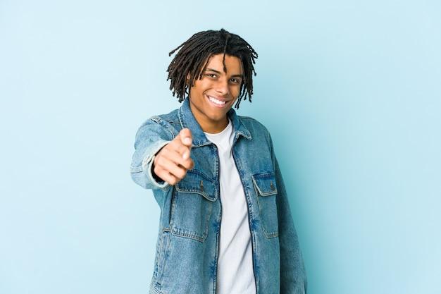 Junger schwarzer mann, der ein fröhliches lächeln einer jeansjacke trägt, zeigt nach vorne.