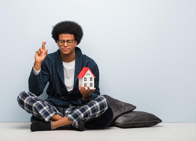 Junger schwarzer mann, der ein hausmodell sitzt auf den bodenüberfahrtfingern für das haben des glücks hält
