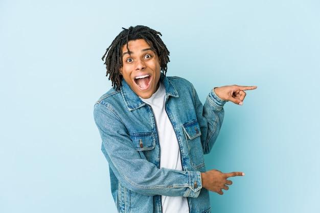 Junger schwarzer mann, der eine aufgeregte jeansjacke mit zeigefingern weg zeigt.
