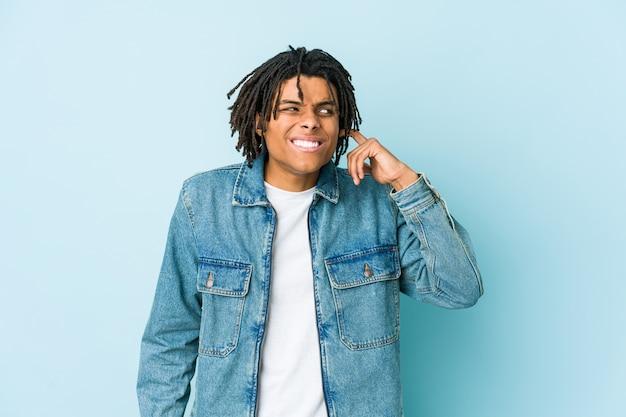 Junger schwarzer mann, der eine jeansjacke trägt, die ohren mit händen bedeckt.