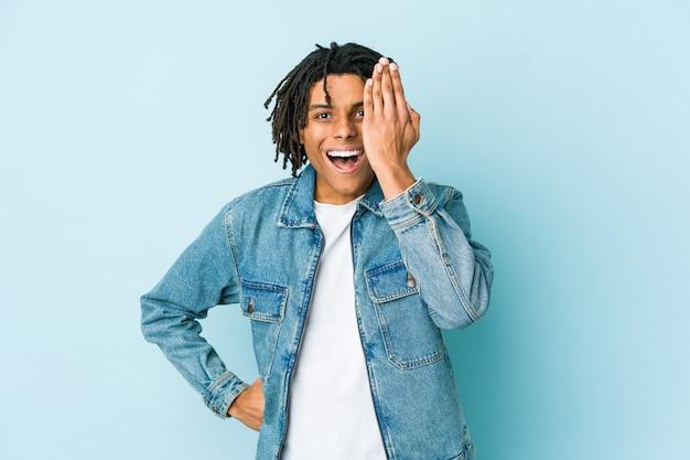Junger schwarzer mann, der eine jeansjacke trägt, die spaß hat, halbes gesicht mit handfläche bedeckend.