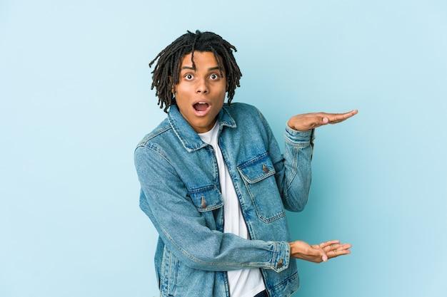 Junger schwarzer mann, der eine jeansjacke trägt, schockiert und erstaunt, einen kopierraum zwischen den händen haltend.