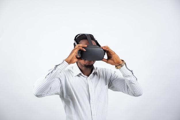 Junger schwarzer mann, der eine virtual-reality-brille aufsetzt