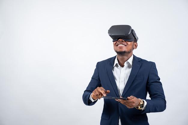 Junger schwarzer mann, der einen anzug trägt und ein virtual-reality-headset und ein telefon verwendet