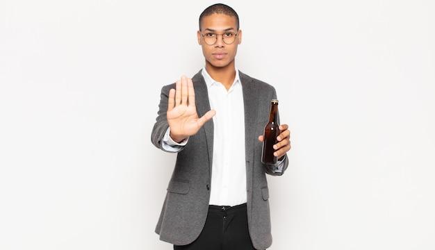 Junger schwarzer mann, der ernst, streng, unzufrieden und wütend aussieht und offene handfläche zeigt, die stoppgeste macht