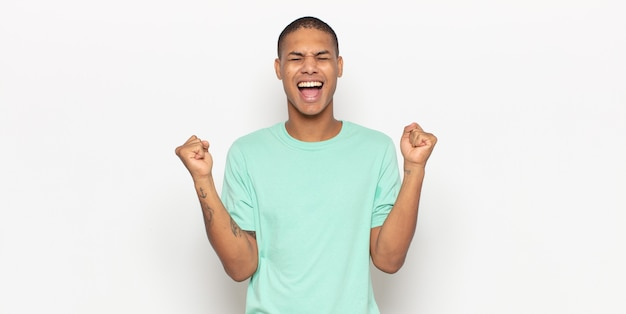 Junger schwarzer mann, der extrem glücklich und überrascht aussieht, erfolg feiert, schreit und springt