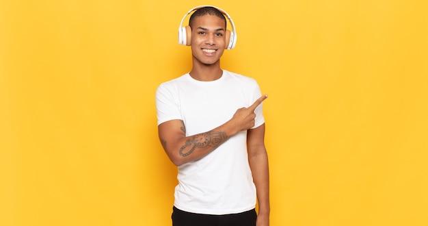 Junger schwarzer mann, der fröhlich lächelt, sich glücklich fühlt und zur seite und nach oben zeigt und objekt im kopienraum zeigt