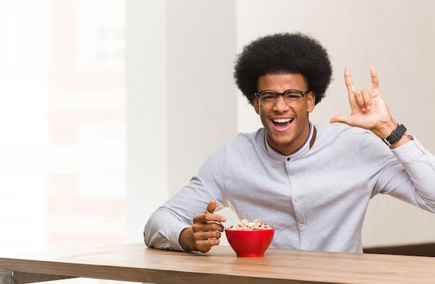 Junger schwarzer mann, der frühstückt, eine felsengeste tuend