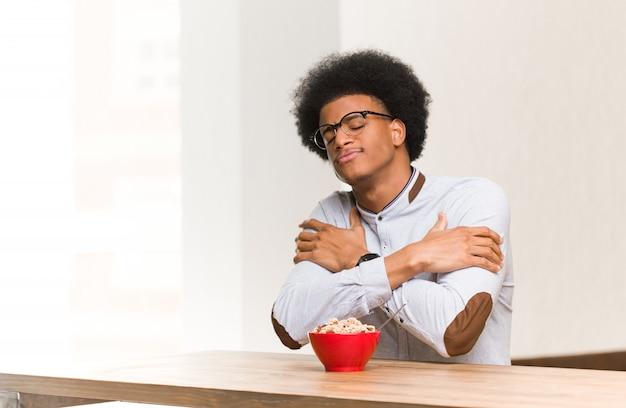 Junger schwarzer mann, der frühstückt, eine umarmung gebend