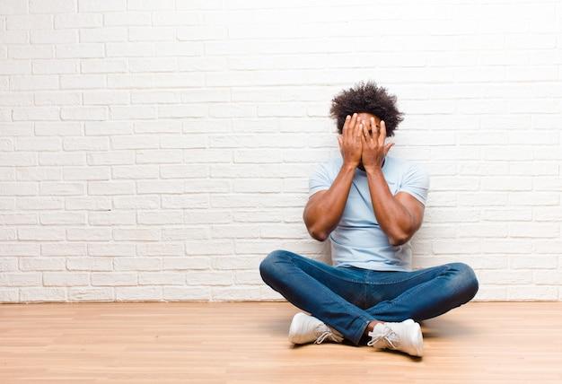 Junger schwarzer mann, der gesicht mit händen bedeckt, mit überraschtem ausdruck zwischen den fingern späht und zur seite schaut, die zu hause auf dem boden sitzt