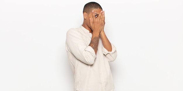 Junger schwarzer mann, der gesicht mit händen bedeckt und mit überraschtem ausdruck zwischen den fingern späht