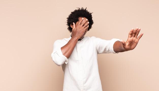 Junger schwarzer mann, der gesicht mit hand bedeckt und andere hand nach vorne legt, um kamera zu stoppen, fotos oder bilder ablehnend