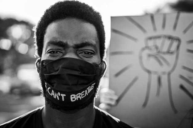 Junger schwarzer mann, der gesichtsmaske während des protestes der gleichberechtigung trägt