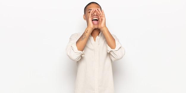 Junger schwarzer mann, der glücklich, aufgeregt und positiv fühlt, einen großen schrei mit den händen neben dem mund gibt und ruft