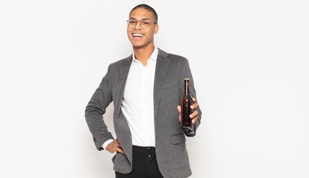 Junger schwarzer mann, der glücklich mit einer hand auf hüfte und selbstbewusster, positiver, stolzer und freundlicher haltung lächelt