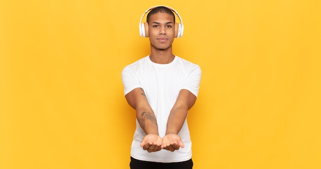 Junger schwarzer mann, der glücklich mit freundlichem, selbstbewusstem, positivem blick lächelt und ein objekt oder konzept anbietet und zeigt