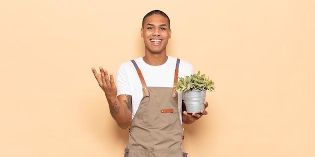Junger schwarzer mann, der glücklich, überrascht und fröhlich fühlt, mit positiver einstellung lächelt und eine lösung oder idee verwirklicht