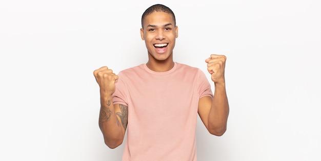 Junger schwarzer mann, der glücklich, überrascht und stolz fühlt, schreit und erfolg mit einem großen lächeln feiert