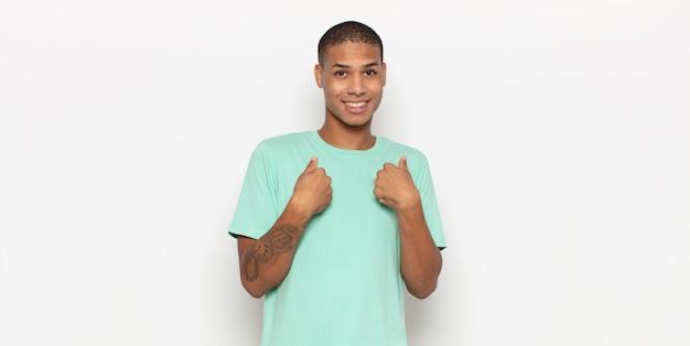 Junger schwarzer mann, der glücklich, überrascht und stolz ist und mit einer aufregung auf sich selbst zeigt