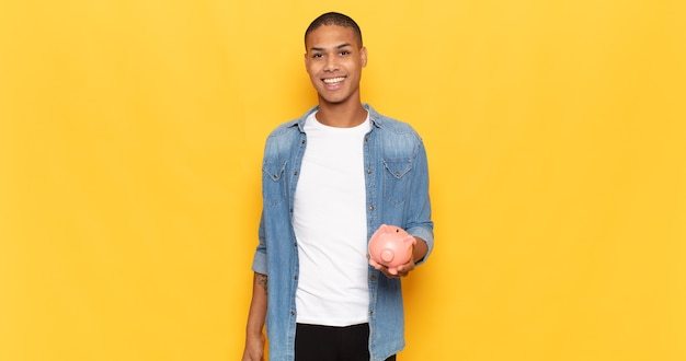 Junger schwarzer mann, der glücklich und angenehm überrascht aussieht, aufgeregt mit einem faszinierten und schockierten ausdruck