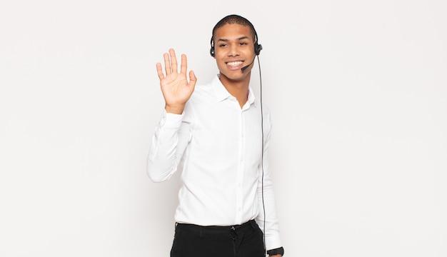 Junger schwarzer mann, der glücklich und fröhlich lächelt, hand winkt, sie begrüßt und begrüßt oder sich verabschiedet