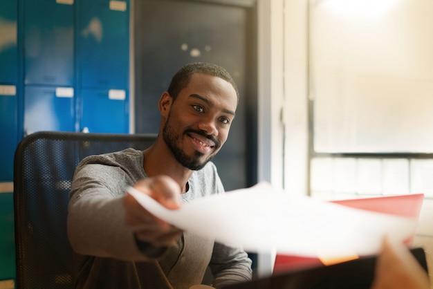 Junger schwarzer mann, der in den modernen büroräumen arbeitet