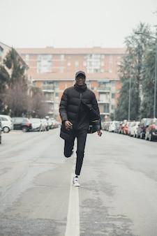 Junger schwarzer mann, der in die straße läuft und weiter schaut