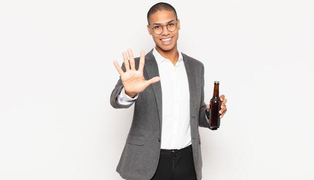 Junger schwarzer mann, der lächelt und freundlich aussieht, die nummer fünf oder fünf mit der hand nach vorne zeigt und herunterzählt