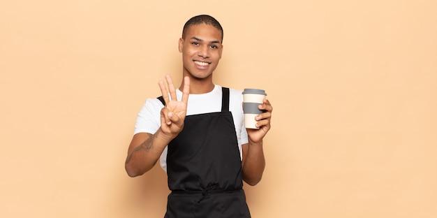Junger schwarzer mann, der lächelt und freundlich aussieht, nummer drei oder dritte mit der hand nach vorne zeigt, herunterzählt