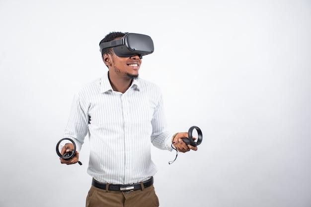 Junger schwarzer mann, der lächelt, während er ein vr-headset und controller verwendet