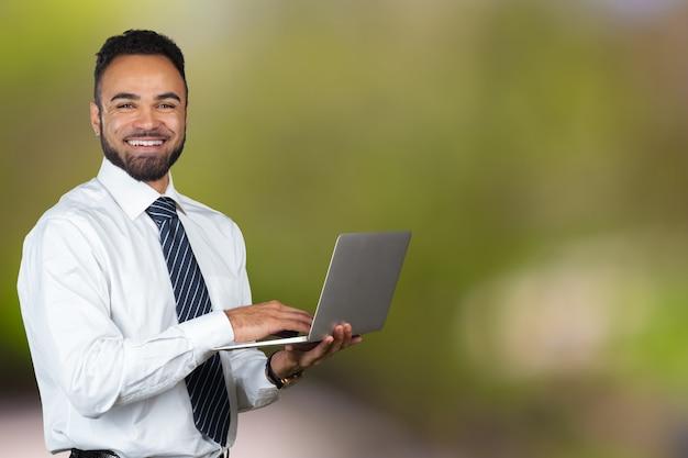 Junger schwarzer mann, der laptop lokalisiertes porträt hält
