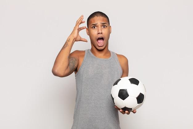 Junger schwarzer mann, der mit den händen in der luft schreit und sich wütend, frustriert, gestresst und verärgert fühlt