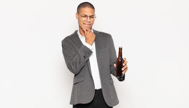 Junger schwarzer mann, der mit einem glücklichen, selbstbewussten ausdruck mit der hand am kinn lächelt, sich wundert und zur seite schaut