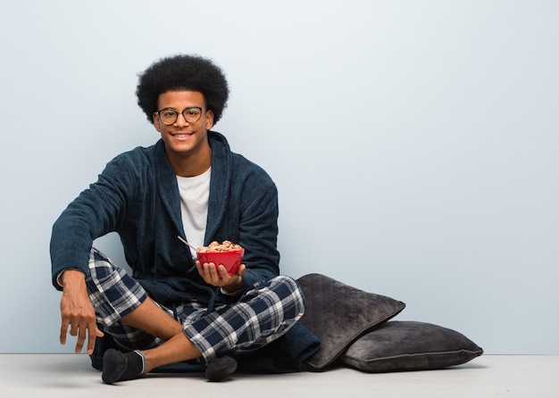 Junger schwarzer mann, der mit einem großen lächeln nett sitzt und frühstückt