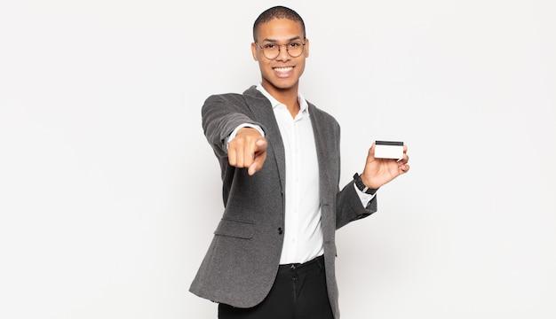 Junger schwarzer mann, der mit einem zufriedenen, selbstbewussten, freundlichen lächeln auf kamera zeigt und sie wählt