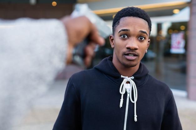 Junger schwarzer mann, der mit gewehr bedroht wird
