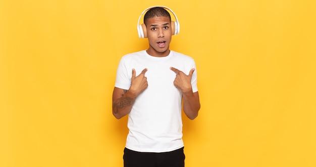 Junger schwarzer mann, der mit offenem mund schockiert und überrascht aussieht und auf sich selbst zeigt