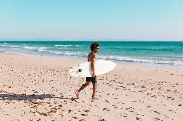 Junger schwarzer mann, der mit surfbrett zum meer kommt