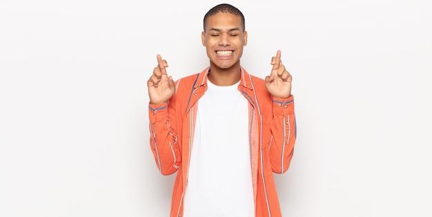 Junger schwarzer mann, der nervös und hoffnungsvoll fühlt, daumen drückt, betet und auf glück hofft