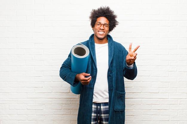 Junger schwarzer mann, der pyjamas mit einer yogamatte trägt