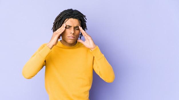 Junger schwarzer mann, der rasta-frisur trägt, die einen kopfschmerz hat und vorderseite des gesichts berührt.